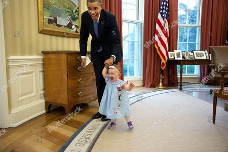"""""""Despite the haphazard framing, I love the expressions on the President and one-year-old Lincoln Rose Smith as she learns to walk in the Oval Office. This moment happened when former Deputy Press Secretary Jamie Smith and her family stopped by for a departure greet and photograph with the President."""" - April 4, 2014"""