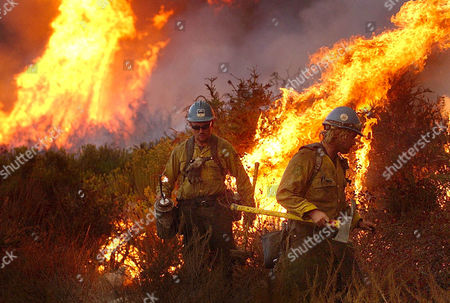 Lassen Hot Shots Tim Troxel, left, and Bobby Willis ignite the back fires to protect homes east of Haven in Rancho Cucamonga