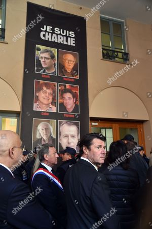 French Deputy and mayor of Nice, Christian Estrosi (C) stands with Rudy Salles (2-L), French Deputy and Deputy mayor of Nice, in front of a poster with the pictures the victims of satirical newspaper Charlie Hebdo at Nice Town Hall
