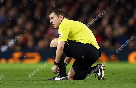 Referee Mr Phil Dowd ties his boot lace