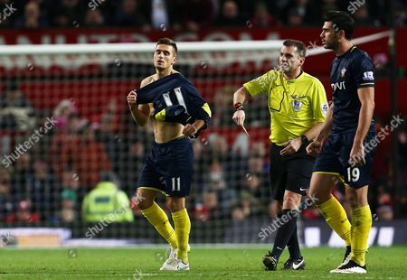Referee Mr Phil Dowd shows Dusan Tadic of Southampton a yellow card after his goal celebration