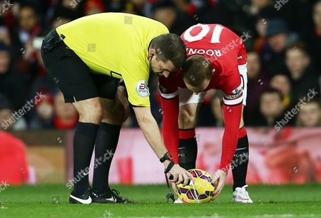 Referee Mr Phil Dowd uses vanishing spray in front of Wayne Rooney of Manchester United