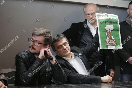 Columnist Patrick Pelloux, also physician and specialist of emergency medical services, center, shows the new cover of French satirical magazine Charlie Hebdo. Next to him is Charlie Hebdo contributor Renald Luzier aka Luz, who drew the cover of the latest issue