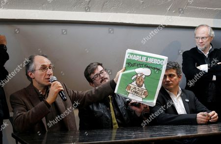 The new chief editor of French satirical magazine Charlie Hebdo, Gerard Biard, left, show the new cover of French satirical magazine Charlie Hebdo with Cartoonist Renald Luzier, known as Luz, center, and columnist Patrick Pelloux, right