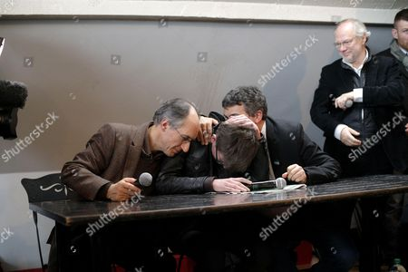 The new chief editor of French satirical magazine Charlie Hebdo, Gerard Biard, left, Cartoonist Renald Luzier, known as Luz, center, and columnist Patrick Pelloux, right, in the presence of the chief editor of Liberation Laurent Joffrin, standing right
