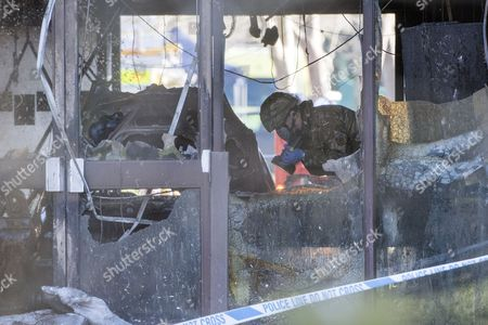 A bomb disposal officer insects a burnt out vehicle in the main reception of the South Oxfordshire District Council building in Crowmarsh Gifford