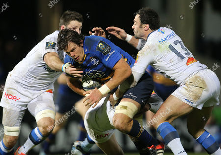 Leinster's Mike McCarthy is tackled by Johnnie Beattie and Thomas Combezou of Castres Olympique