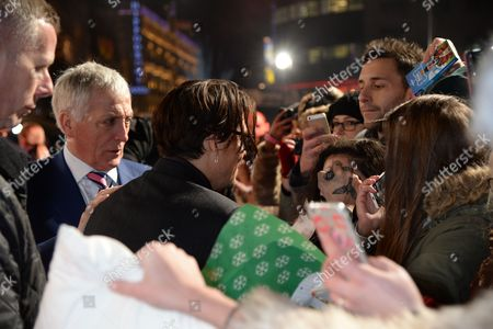 Stock Photo of Johnny Depp signing a fan's face with bodyguard Jerry Judge