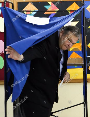 PASOK leader Evangelos Venizelos emerges from the screen to vote in Thesaloniki