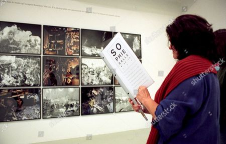 Exhibition goer looking at pictures from burnt negatives