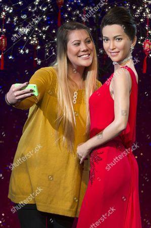 A fan taking a selfie photo with a waxwork of Li Bingbing