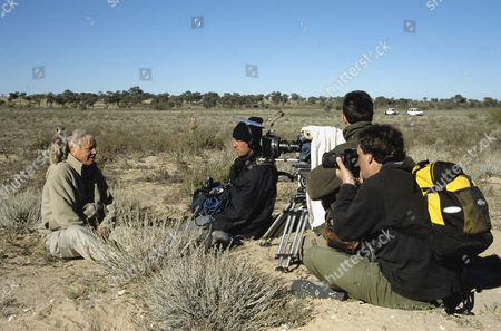 Stock Photo of Sir David Attenborough with meerkat on shoulder being filmed for BBC series Life of Mammals, producer Huw Cordey at front right, Kalahari Desert, Northern Cape, South Africa