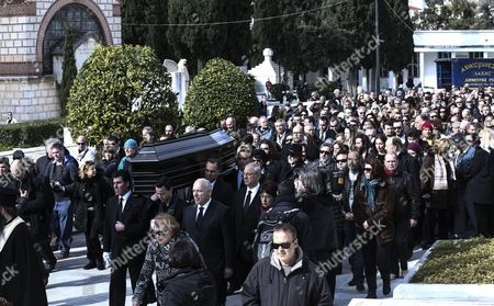 Followed by mourners, pallbearers carry the coffin of singer Demis Roussos during his funeral procession in Athens