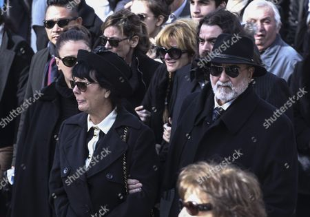 Demis Roussos' wife Anne Marie and brother Costas, right  exit the church in the funeral procession for singer Demis Roussos, in Athens