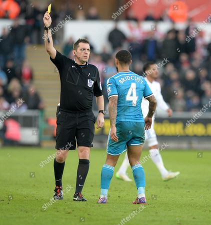 Referee Phil Dowd books Sunderland's Liam Bridcutt after his tackle on Swansea City's Nathan Dyer