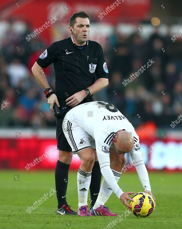 Stock Photo of Referee Phil Dowd stands behind Jonjo Shelvey of Swansea City as he places the ball for a free kick