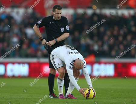 Referee Phil Dowd stands behind Jonjo Shelvey of Swansea City as he places the ball for a free kick