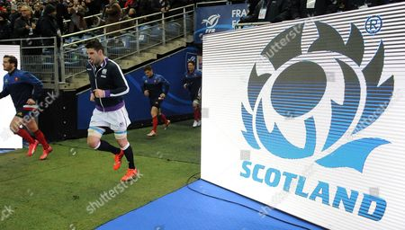 Scotland player Johnnie Beattie runs onto the field for the start of the match.