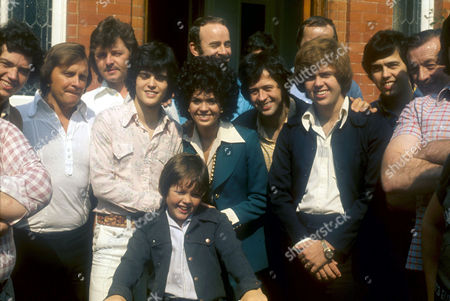 L TO R JAY, DONNY, MARIE, JIMMY, WAYNE, MERRYLL, ALAN OSMOND WITH BODYGUARDS OUTSIDE THE HIDEAWAY HOUSE NEAR LONDON, BRITAIN - SEP 1974