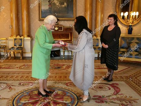 Queen Elizabeth II (left) presents Imtiaz Dharker with The Queen's Gold Medal for Poetry, as Poet Laureate Carol Ann Duffy looks on