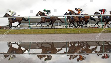 Stock Photo of WESTERLY (Seb Sanders) leads the field past the stands on her way to winning The 32RedBingo Handicap on a wet day at Lingfield