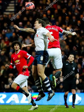 Kevin Davies of Preston North End wins a header against Marcos Rojo of Manchester United