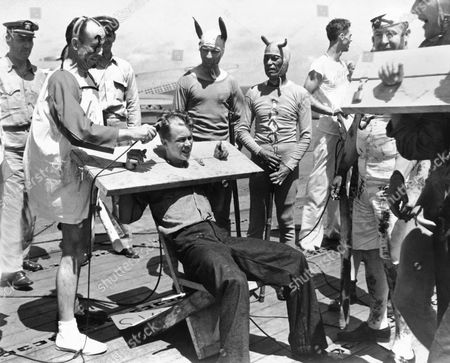 Stock Photo of Pacific Ocean: October 15, 1942 Members of the court of Neptunus Rex, Ruler of the Raging Main, convene on the deck of a U.S. Navy aircraft carrier as it approches the equator. The court is in action to convert the 'pollywogs' (men who have never crossed the equator) into 'shellbacks', once they have completed the rituals. Here one of the pollywogs is being shorn by another pollywog who has already suffered the indignity.