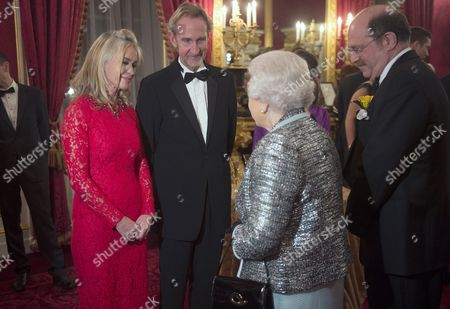 Stock Image of Queen Elizabeth II meets Mike Rutherford and his wife Angie Rutherford