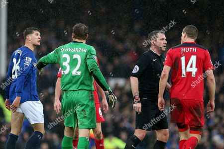Stock Picture of Mark Schwarzer of Leicester City holds off John Stones of Everton  as referee Mr. Phil Dowd speaks to Robert Huth of Leicester City