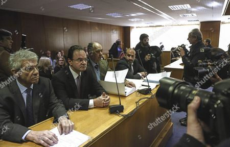 Former Greek finance minister Giorgos Papakonstantinou, second left, sits in court next to his lawyers