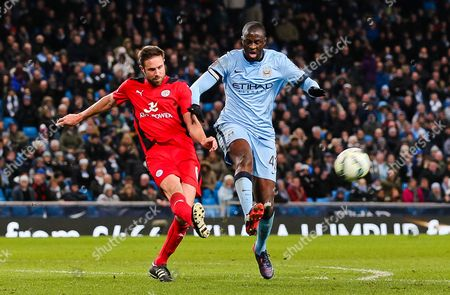Manchester City's Yaya Toure is challenged by Matthew Upson of Leicester City