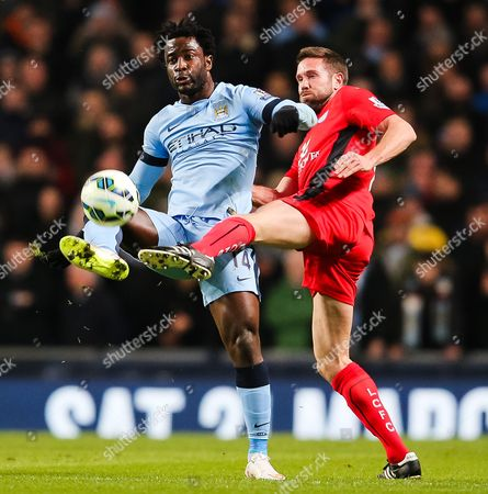 Matthew Upson of Leicester City challenges Manchester City's Wilfried Bony
