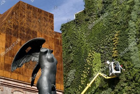 Caixa Forum, by the architects Herzog & de Meuron, with sculpture by sculptor Igor Mitoraj and worker in the vertical garden by Patrick Blanc, Paseo del Prado, Madrid, Spain, Europe