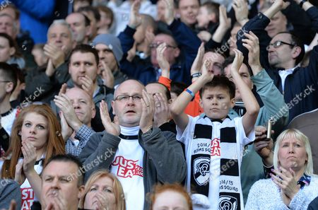 An older Derby County fan with tears in his eyes joins in the applause with a younger fan as they pay tribute to former player Dave Mackay who passed away