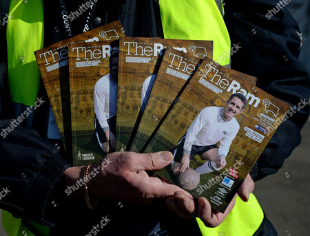 A programme seller outside the iPro Stadium with the cover dedicated as a tribute to former player Dave Mackay who passed away