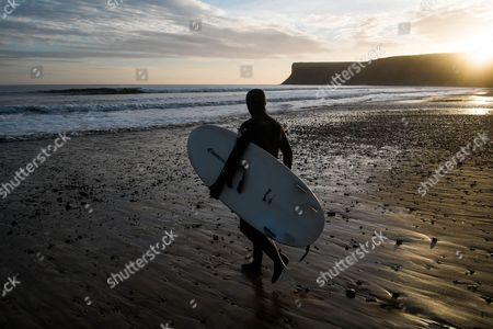 Surfer Sam Davis walks out for an early morning surf as the sun rises over Huntcliff at Saltburn by the Sea