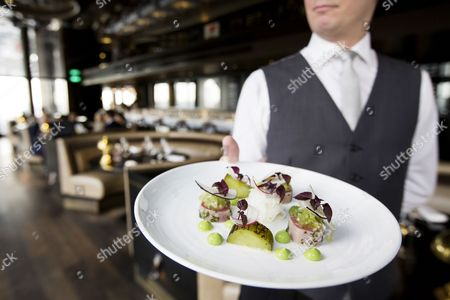 A waiter holds a tuna starter at the City Social Restaurant, ran by Chef Jason Atherton in the Tower 42 building