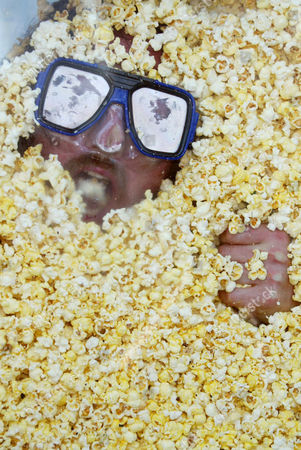 Renowned competitive eater Crazy Legs Conti is buried alive under 100 cubic feet of popcorn inside a life sized popcorn box known as 'The Popcorn Sarcophagus' at the United Artist Battery Park Theatre. Conti breathed through a custom fitted snorkel as he ate, and was equipped with an emergency communication system in the case he became overwelmed by the popcorn. Green for 'all systems go', red for 'danger' and yellow for 'alert / need more butter' Conti sought to eat his way out of the box in time for the premiere of the documentary 'Crazy Legs Conti - Zen and the Art of Competitive Eating'.