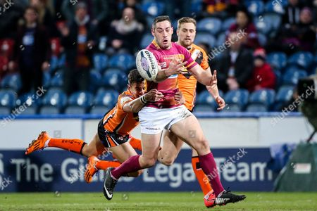 Stock Image of Huddersfield's Joe Wardle is tackled by Castleford's Michael Channing.