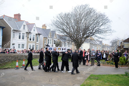 The coffin is carried into All Saints Church