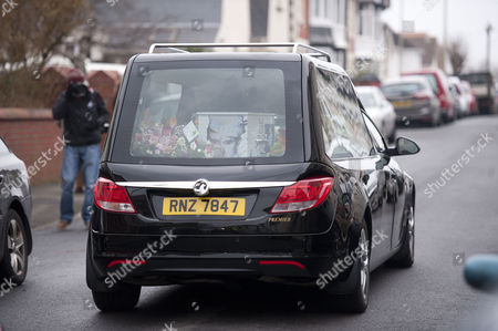The hearse carrying the coffin leaves All Saints Church