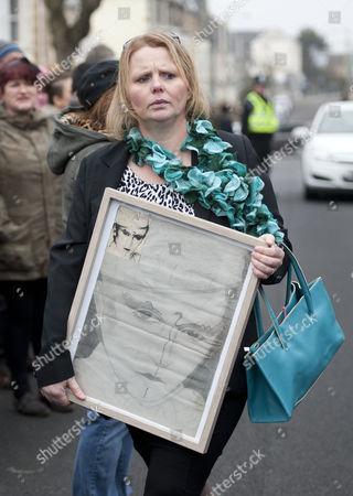 Mourner with a framed picture of Steve Strange