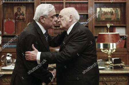 Outgoing Greek President Karolos Papoulias (R) kisses newly elected President of the Republic Prokopis Pavlopoulos (L) during a handover ceremony
