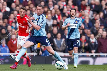 Mesut Ozil of Arsenal takes on Kevin Nolan and Matthew Jarvis of West Ham United