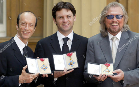 Robin Gibb (left) and Barry Gibb (right) hold their CBEs along with Adam Gibb who received the honour on behalf of his father, the late Maurice Gibb