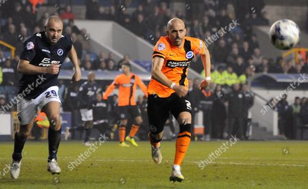 Stock Photo of Bruno Saltor and Gary Taylor-Fletcher chase down the loose ball during the Sky Bet Championship match between Millwall and Brighton and Hove Albion at The Den, London