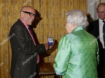 Queen Elizabeth II is presented with a commemorative Winston Churchill Medallion from its designer, artist Brian Clarke