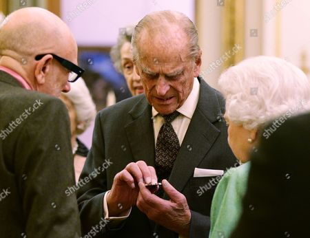 Prince Philip examines a commemorative Winston Churchill Medallion by designer Brian Clarke (left), as Queen Elizabeth II looks on