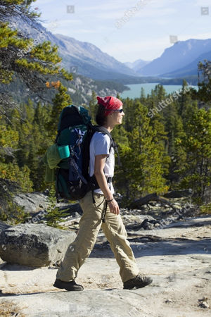 MODEL RELEASED Young woman hiking, backpacking, hiker with backpack, historic Chilkoot Trail, Chilkoot Pass, Lake Bennett behind, Yukon Territory, British Columbia, B. C., Canada