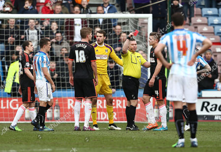 Referee Mr Richard Clark shows Shaun Hutchinson of Fulham a red card after originally showing it to Cauley Woodrow